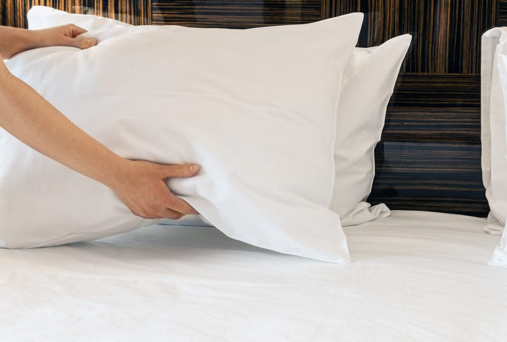 hands placing pillows on the bed