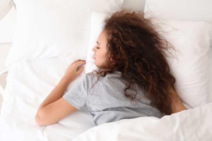 Morning of young African-American woman sleeping in bed