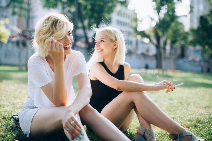 two women at the park smoking cigarettes