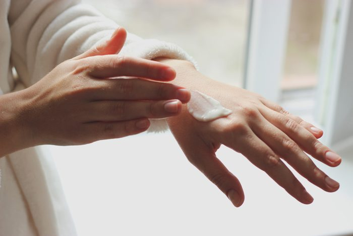 woman putting lotion or sunscreen on hand