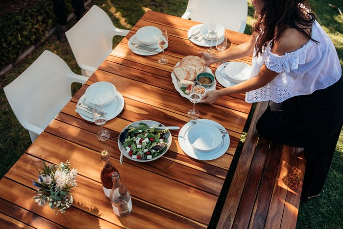 woman setting food on table for party