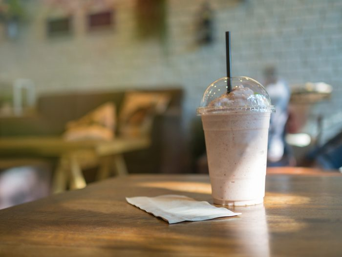 Smoothie with straw in plastic cup on table