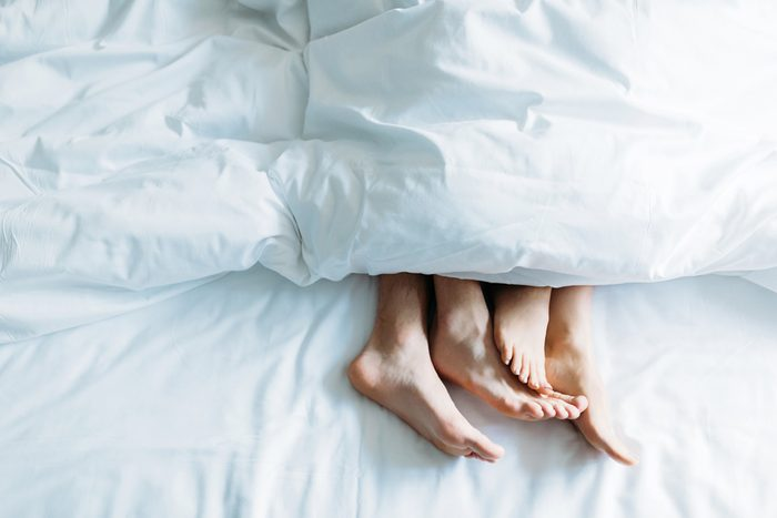 couple's feet under a comforter in bed