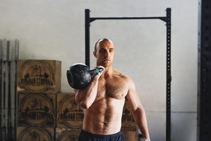 Fitness man doing exercises with kettlebell in gym
