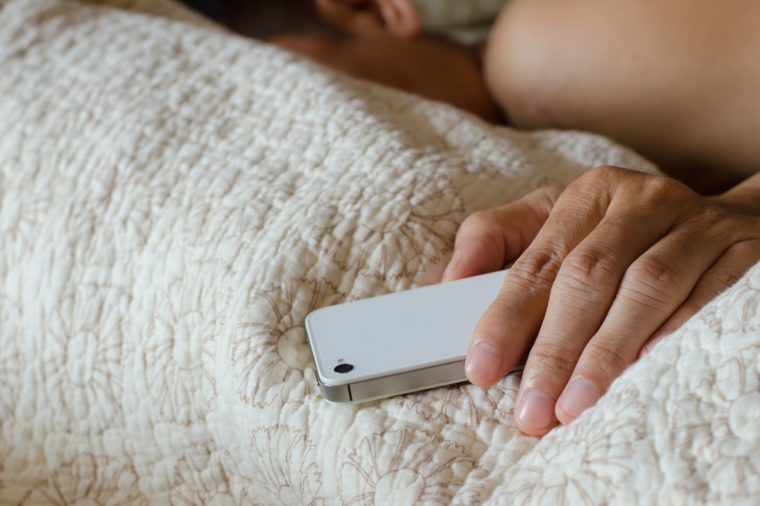 Man sleeping in bed and holding a cell phone.