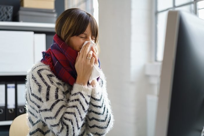 Sick businesswoman with seasonal winter flu blowing her nose in a tissue as she sits at her desk in a warm thick woollen scarf