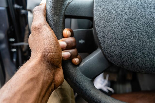 Hand holding steering wheel