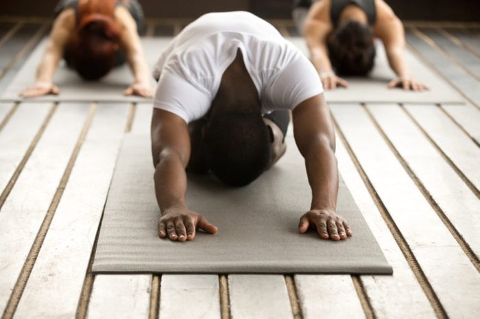 Young black man and group of young sporty people practicing yoga lesson with instructor, stretching in Child exercise, Balasana pose, working out, indoor, studio