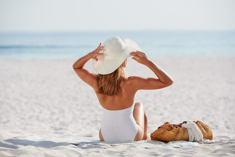 woman sitting at beach wearing hat