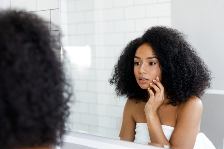 Woman looking in the bathroom mirror, touching her face