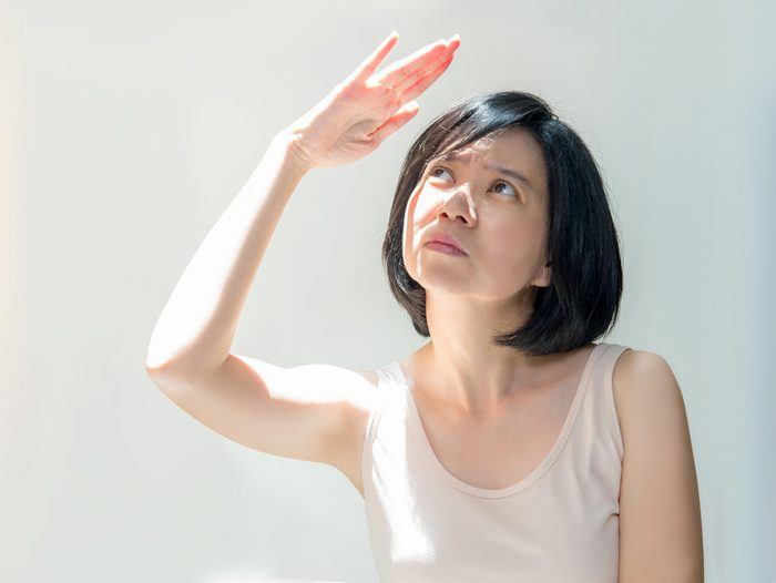 Portrait of a beautiful Asian girl with short black hair covering face by hand of bright sun light. Middle aged woman in a beige dress protecting her face from solar light. Skin care or beauty concept