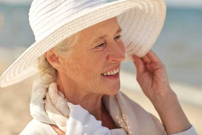 older woman smiling and wearing sun hat