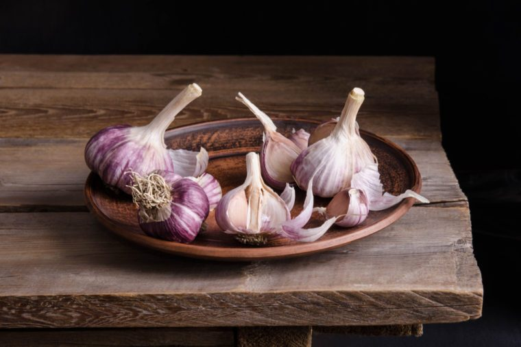 Purple-tinged garlic cloves on a plate on an old wooden table