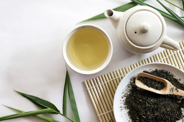 teapot and cup of herbal green tea on bamboo matt
