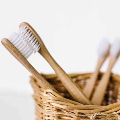 A family set of four wooden bamboo toothbrushes in a straw basket . Two toothbrushes are like parents in love kissing and in focus, and other two - are like children and blurred
