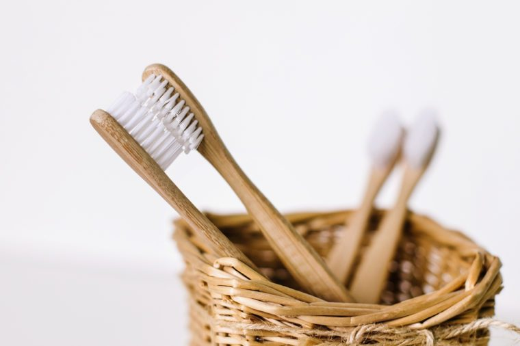 Four wooden bamboo toothbrushes in a straw basket.