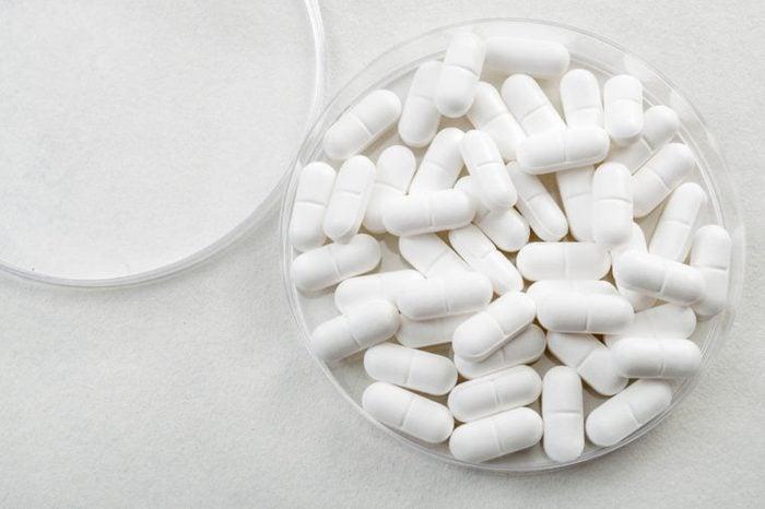 White medical pills in a petri dish.