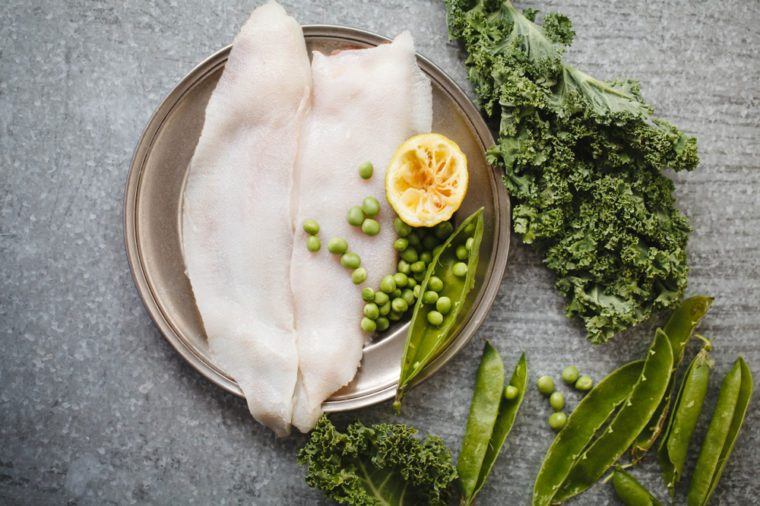 Raw megrim fish fillet with green vegetables.