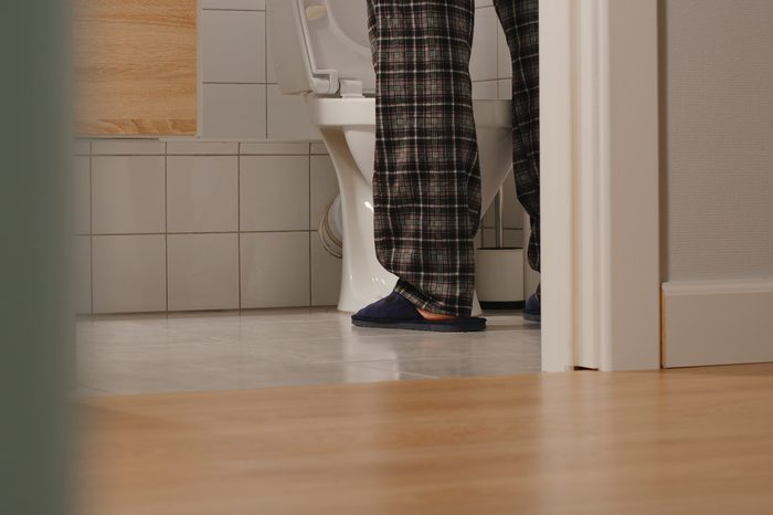 cropped shot of man using the toilet at night