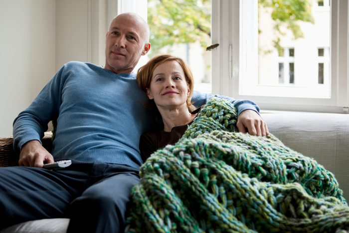 couple sitting on couch at home watching television