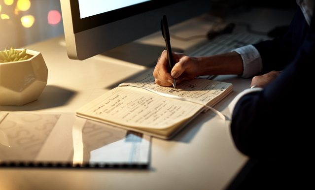 close up of woman writing in notebook at night