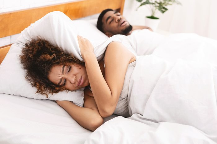 snoring man and woman covering ears with pillow