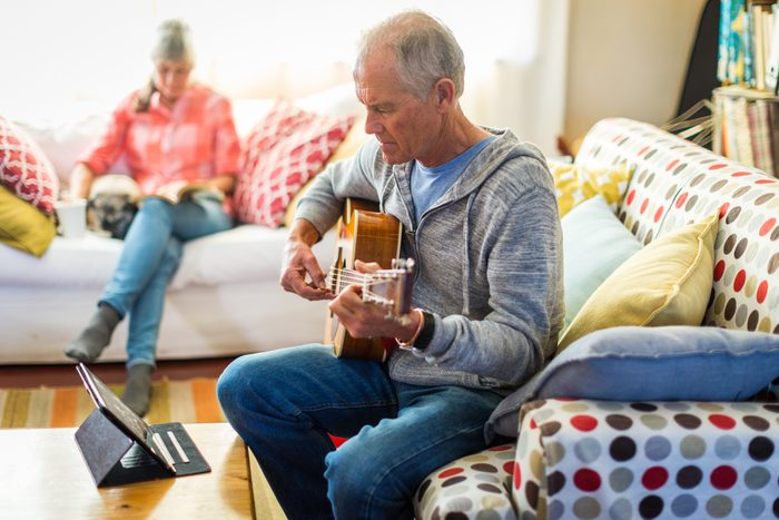 man learning how to play the guitar at home