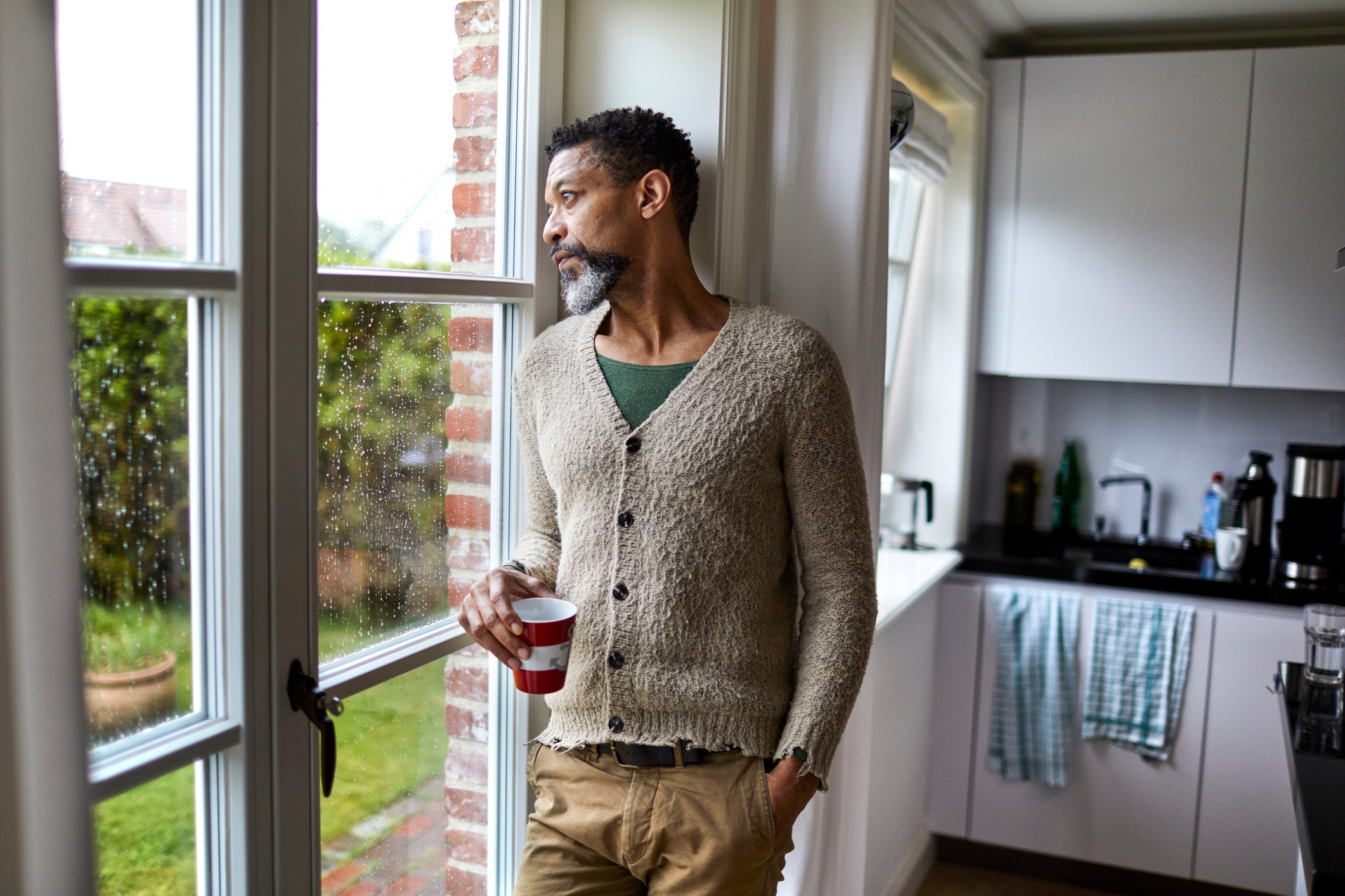 man looking pensively out window