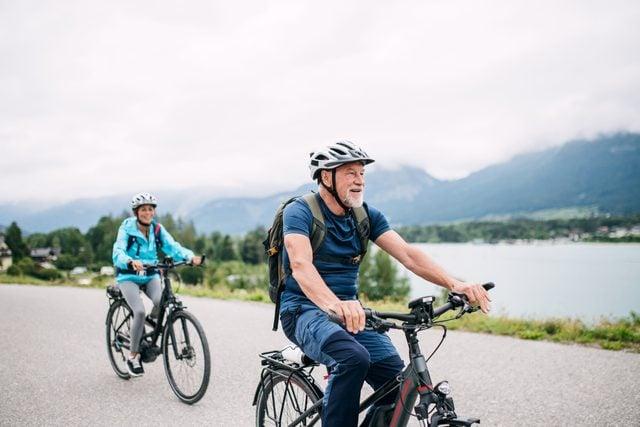 senior couple riding bikes outside for exercise
