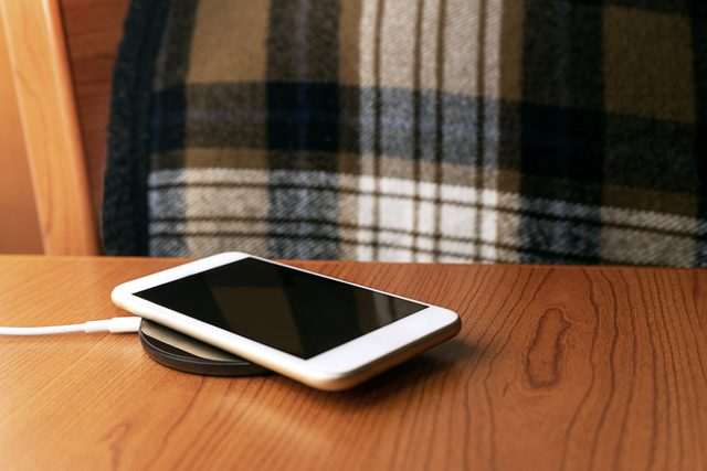 mobile smartphone charging on bed side table at night