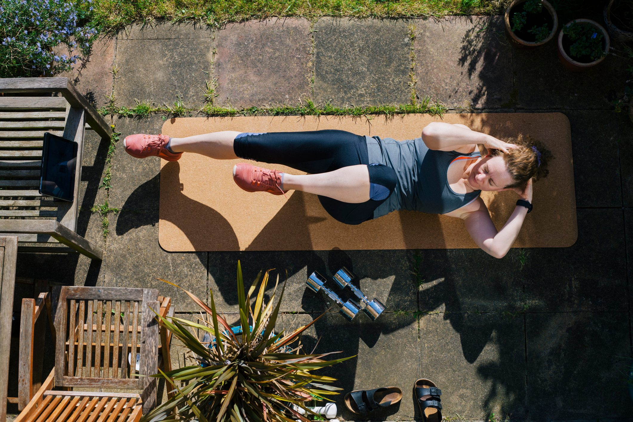 overhead view of woman working out on exercise mat outside