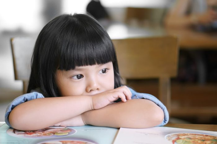 Asian children cute or kid girl lonely and sad with tears in the eye on food table because miss mom and dad or parents do not care with thinking something