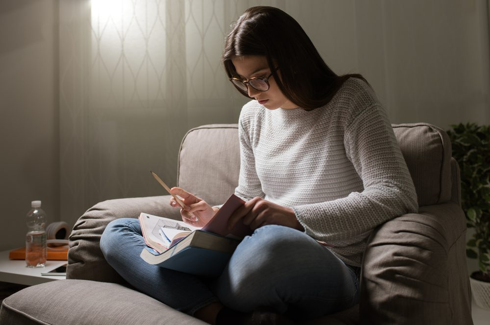 Young woman studying late at night at home, she is sitting on the armchair and reading a book, education and deadlines concept