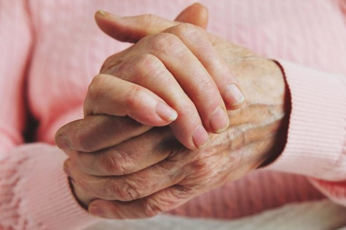 closeup of an elderly person clasping her hands