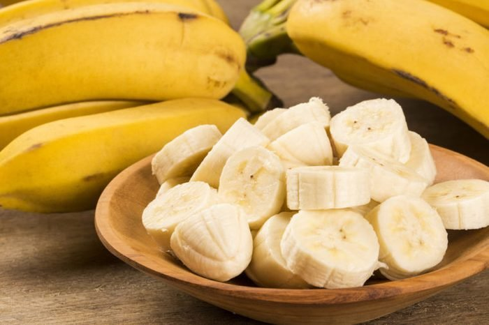 A bunch of bananas and a sliced banana in a bowl on a table.
