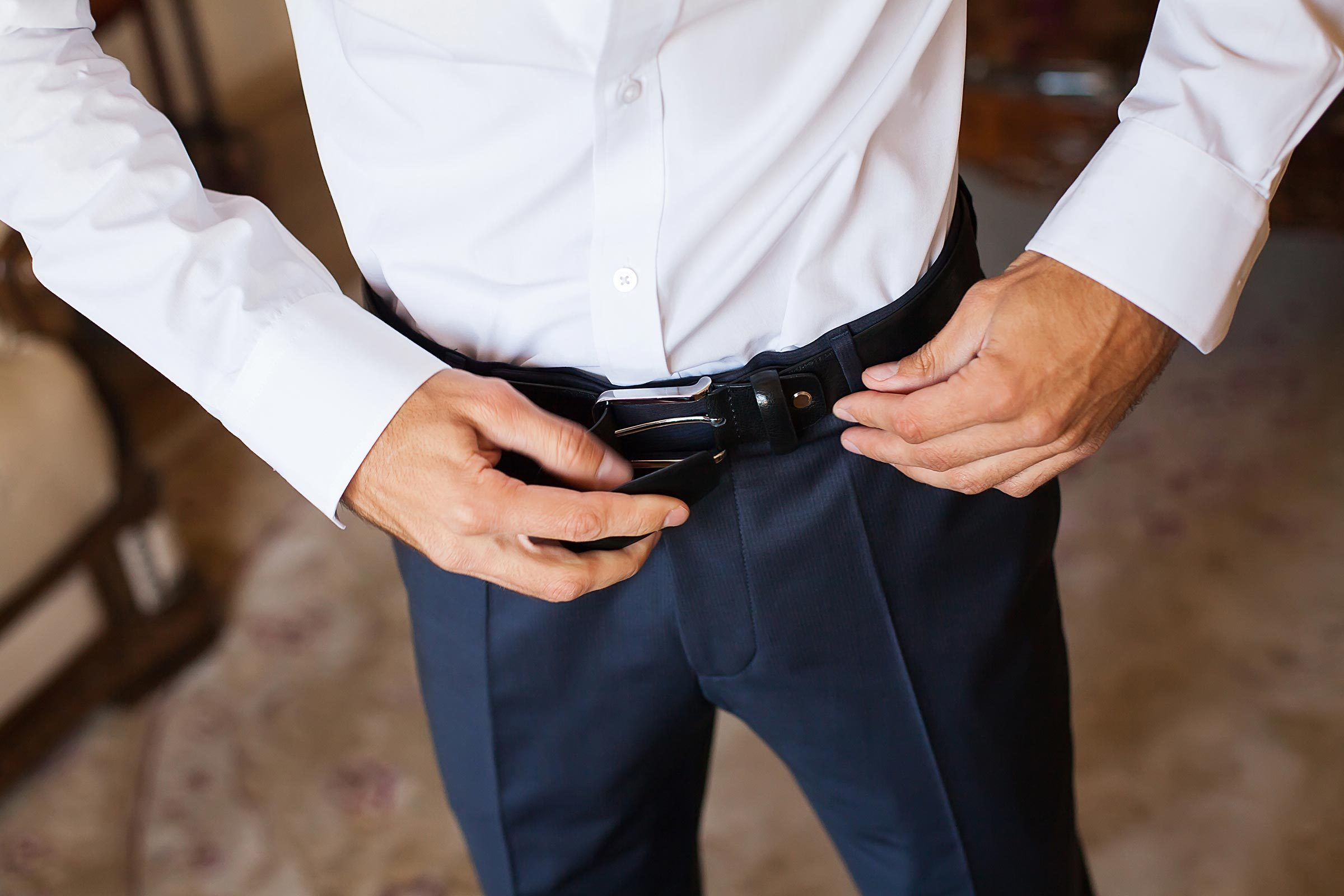 man tightening his belt