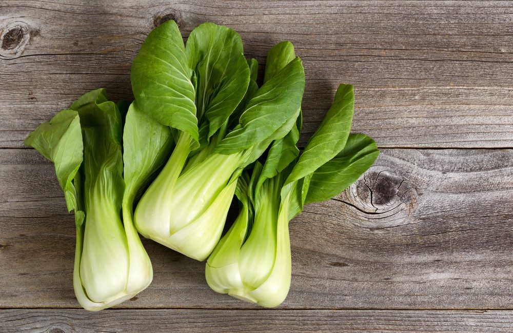 Three bok choy on a wooden background