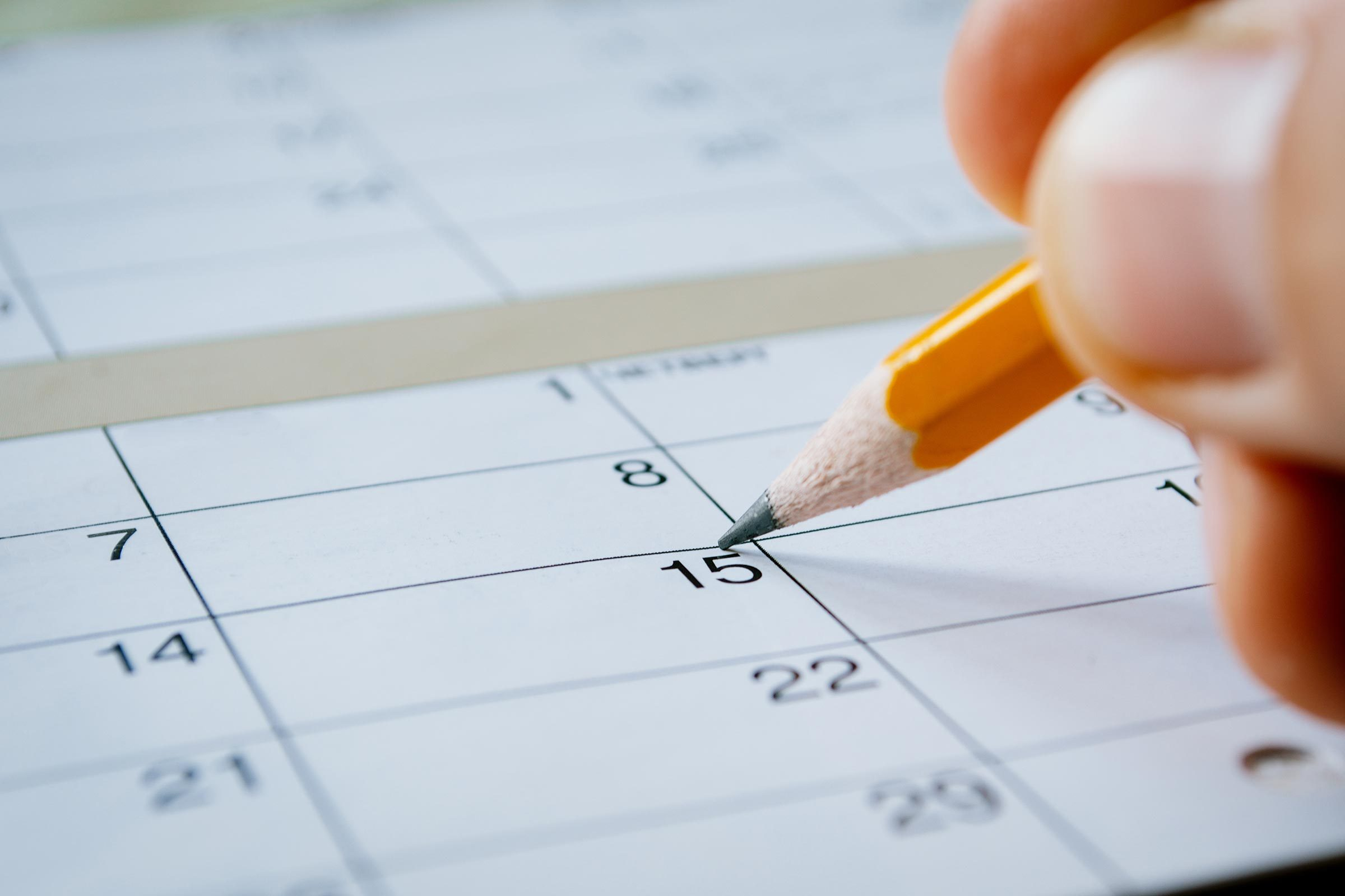 person writing in pencil on a calendar