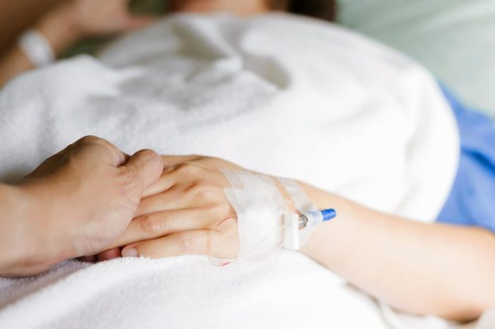 Person lying in a hospital bed with an IV drip on their hand.