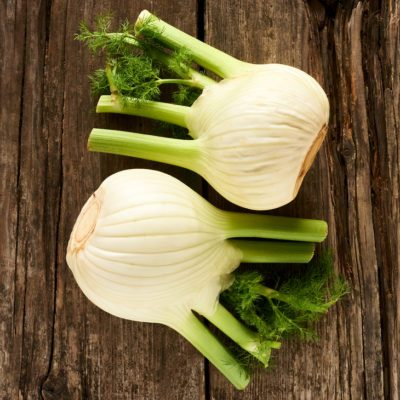 fresh fennel leaning on an old wooden table