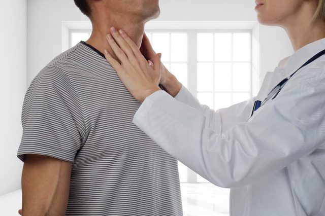 doctor checking man's lymph nodes in neck