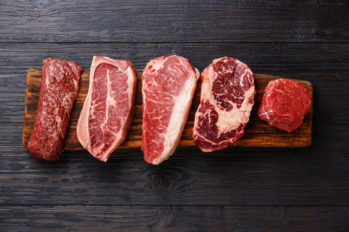 different cuts of red meat on a wooden cutting board