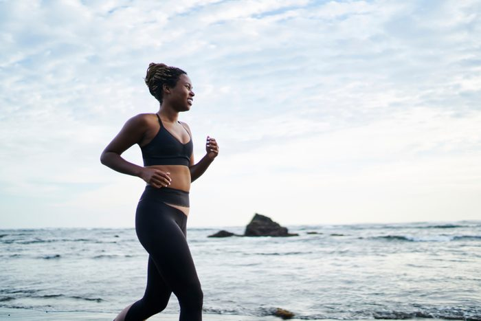 Side view of African American female jogger dressed in stylish sport clothes running along coastline washed by ocean water. Sportive fit woman with dark skin doing morning cardio training on seashore