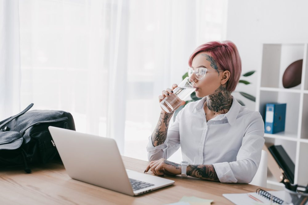 young businesswoman with tattoos drinking water and using laptop at workplace