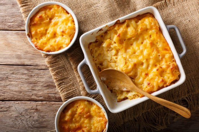 American casserole macaroni and cheese in baking dish close up on the table. Horizontal top view from above