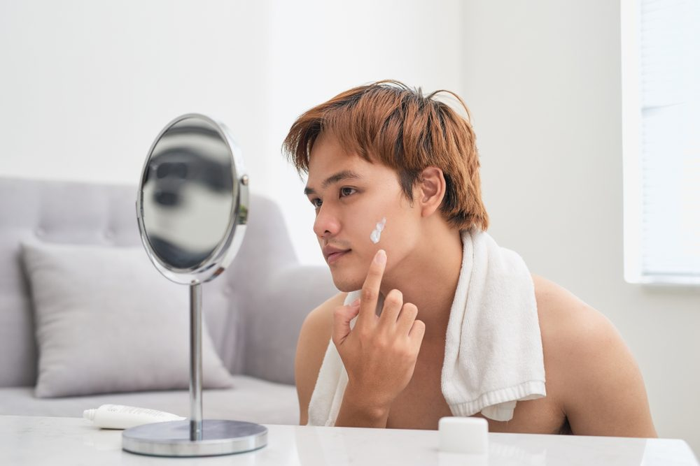 Handsome man looking at himself in mirror and applying cream lotion on face.