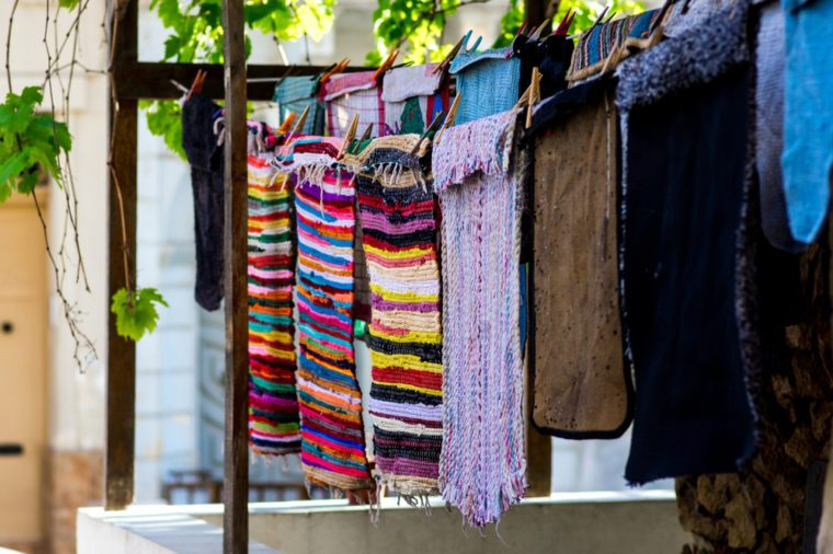 Colorful rugs and mats hanging on a clothing line near the house