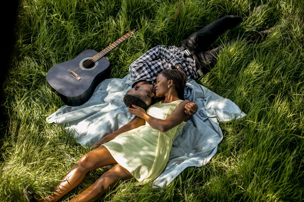 Beautiful fun happy smiling African American couple laying in grass