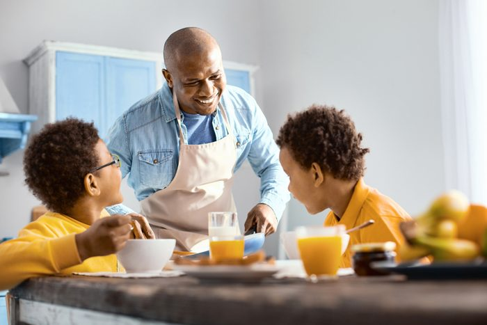 Happy family. Cheerful young man talking to his children and offering them omelet while they eating breakfast