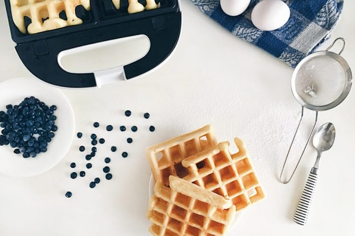 Making Belgian waffles at home - waffle iron, kitchenware and ingredients - fresh blueberry, eggs and flour.